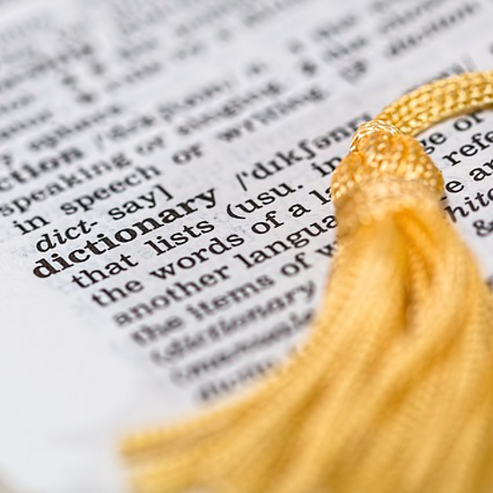 Dictionary page in book with yellow tassel