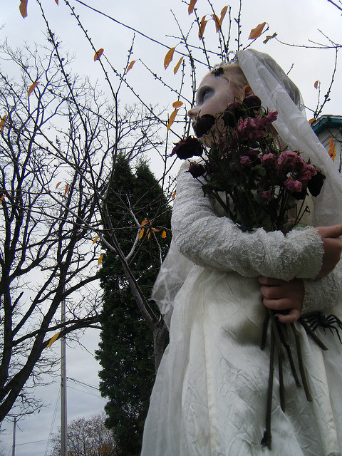 corpse ghost ghostly bride in gray white wedding dress with dead flowers