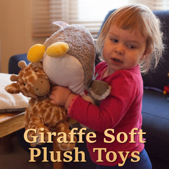 toddler child with soft plush toys giraffe