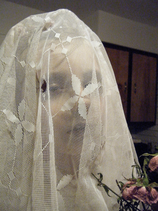 White wedding veil over the face with a hole in to look worn