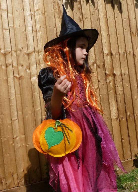 girl dressed up as a witch for Halloween with a pumpkin bag