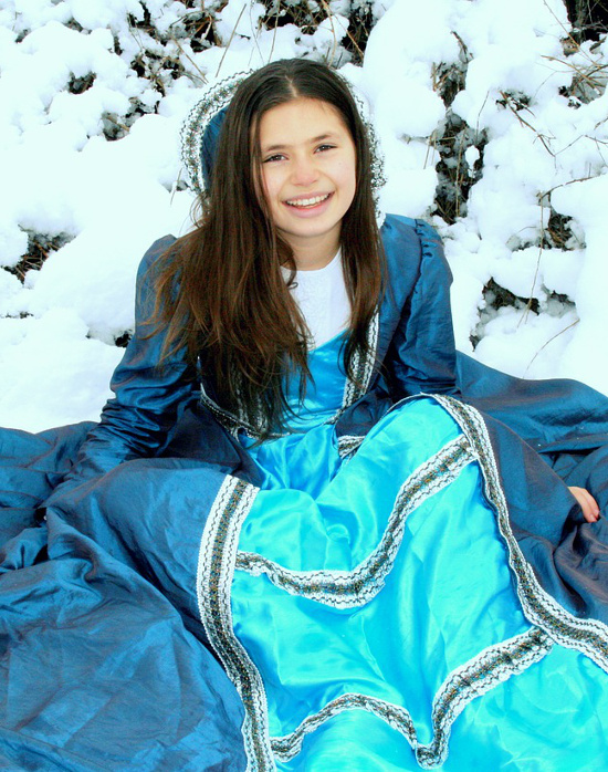 Girl sat in snow in blue dress