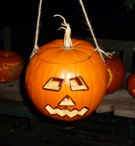 lit carved pumpkin hanging up Jack O lantern face