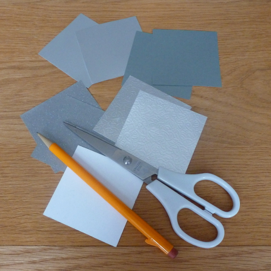 Cutting out squares of silver colored paper for DIY folding papercraft craft