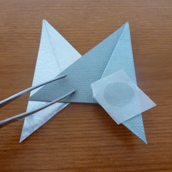 placing the glue dot paper folded star ornament