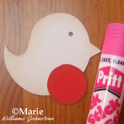 Using Pritt stick adhesive glue to stick on the red card to the paper bird