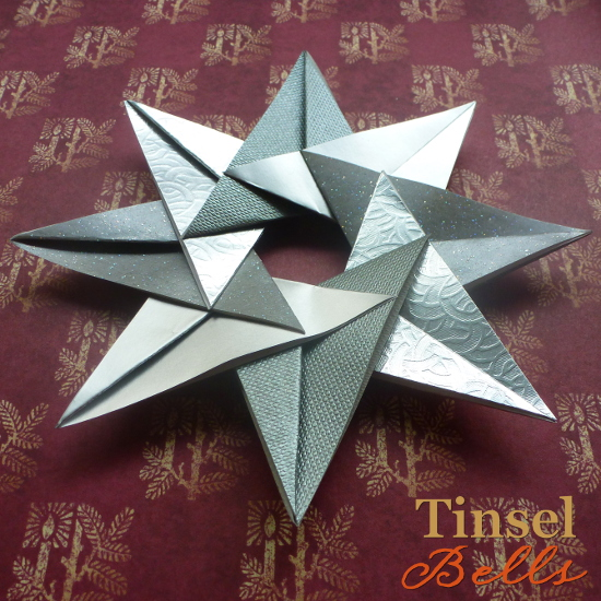 silver 8 pointed paper star on red festive paper with gold candles