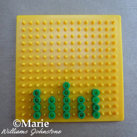 Starting pattern of green beads on yellow pegboard Perler Hama fused