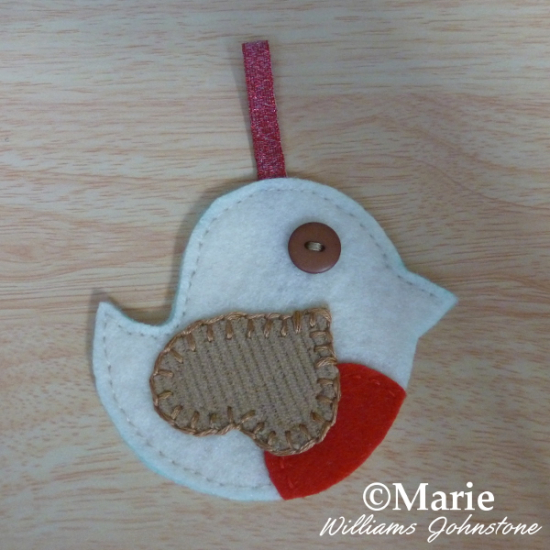 Sewing backstitch around the small festive bird plushie decoration
