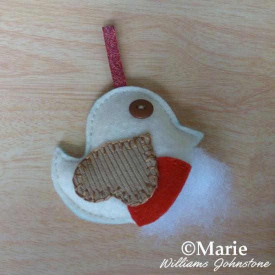 Adding fiber fill toy stuffing inside the mini festive hanging ornament bird red cream colors