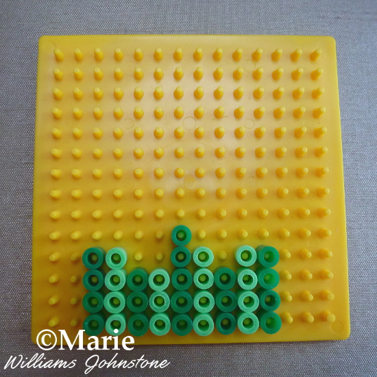Dark and light green fused Perler Hama beads on a board